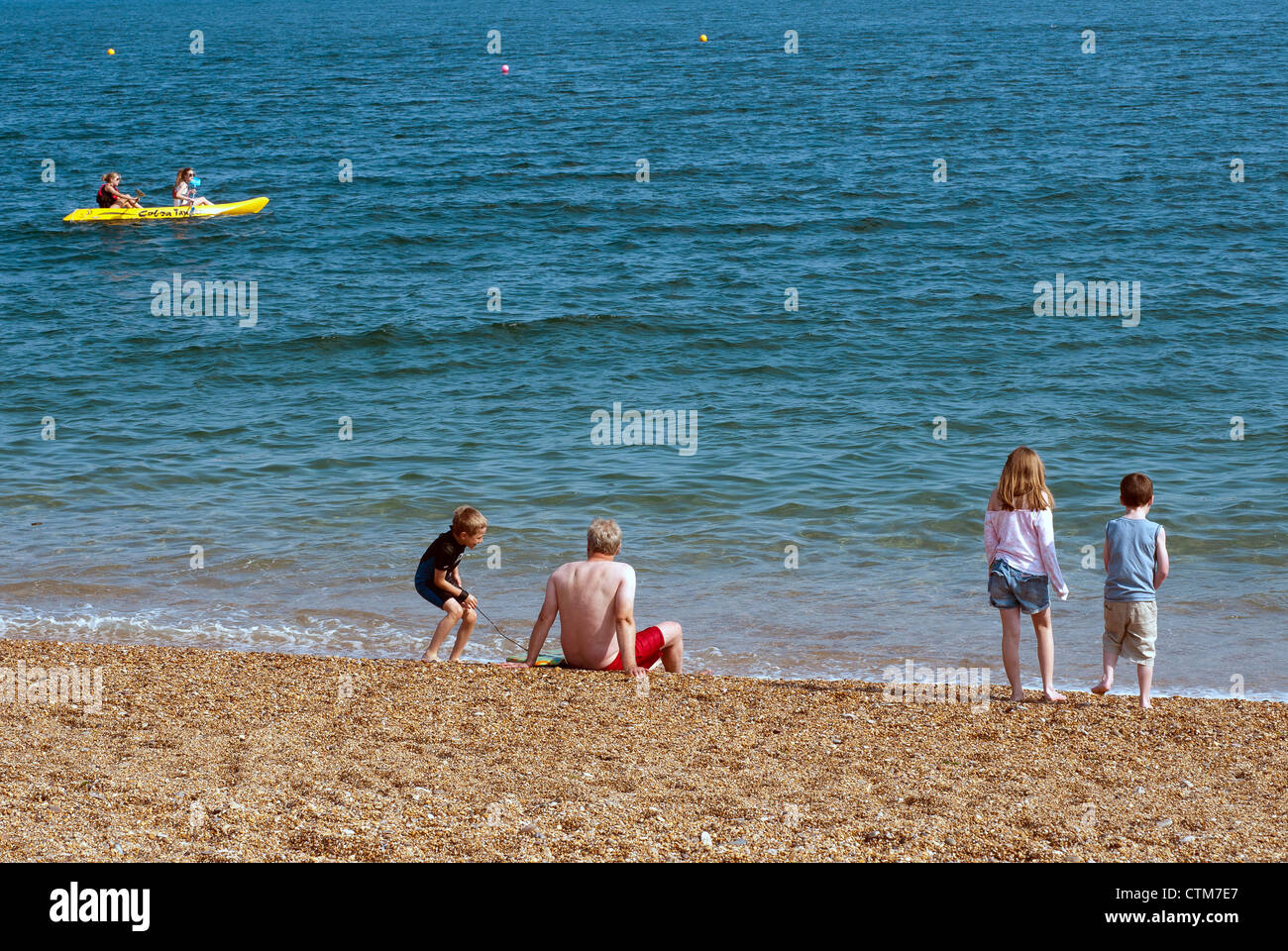 siblings paddling at Blackpool Sands, boats, coast, devon,childhood,staycation, ocean, rock, sand, sea, waves, action, - Stock Image