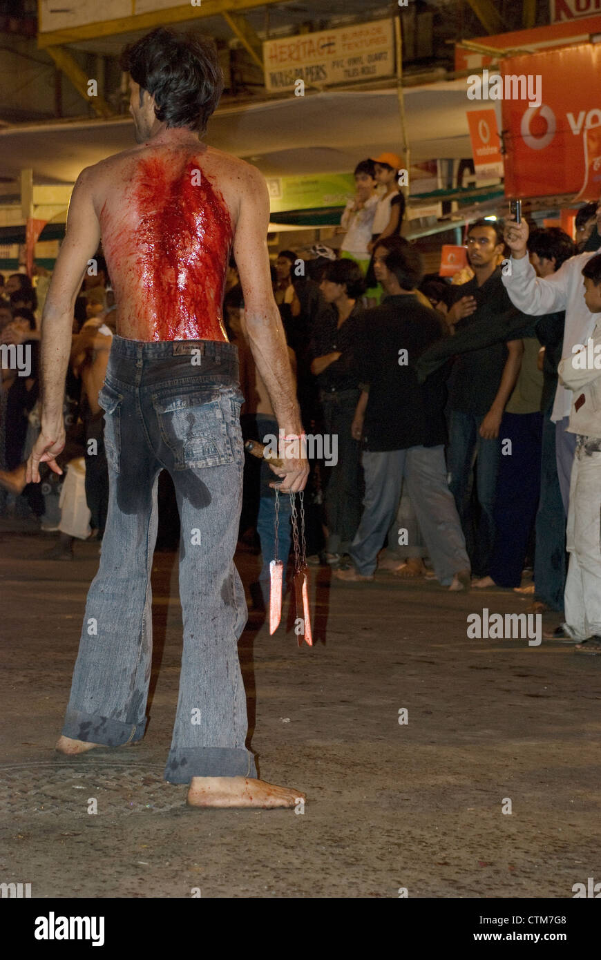 Bloodied devoted Shiite Muslim standing with his knives used to flagellate himself - Ashura festival, Mumbai, Maharashtra. - Stock Image