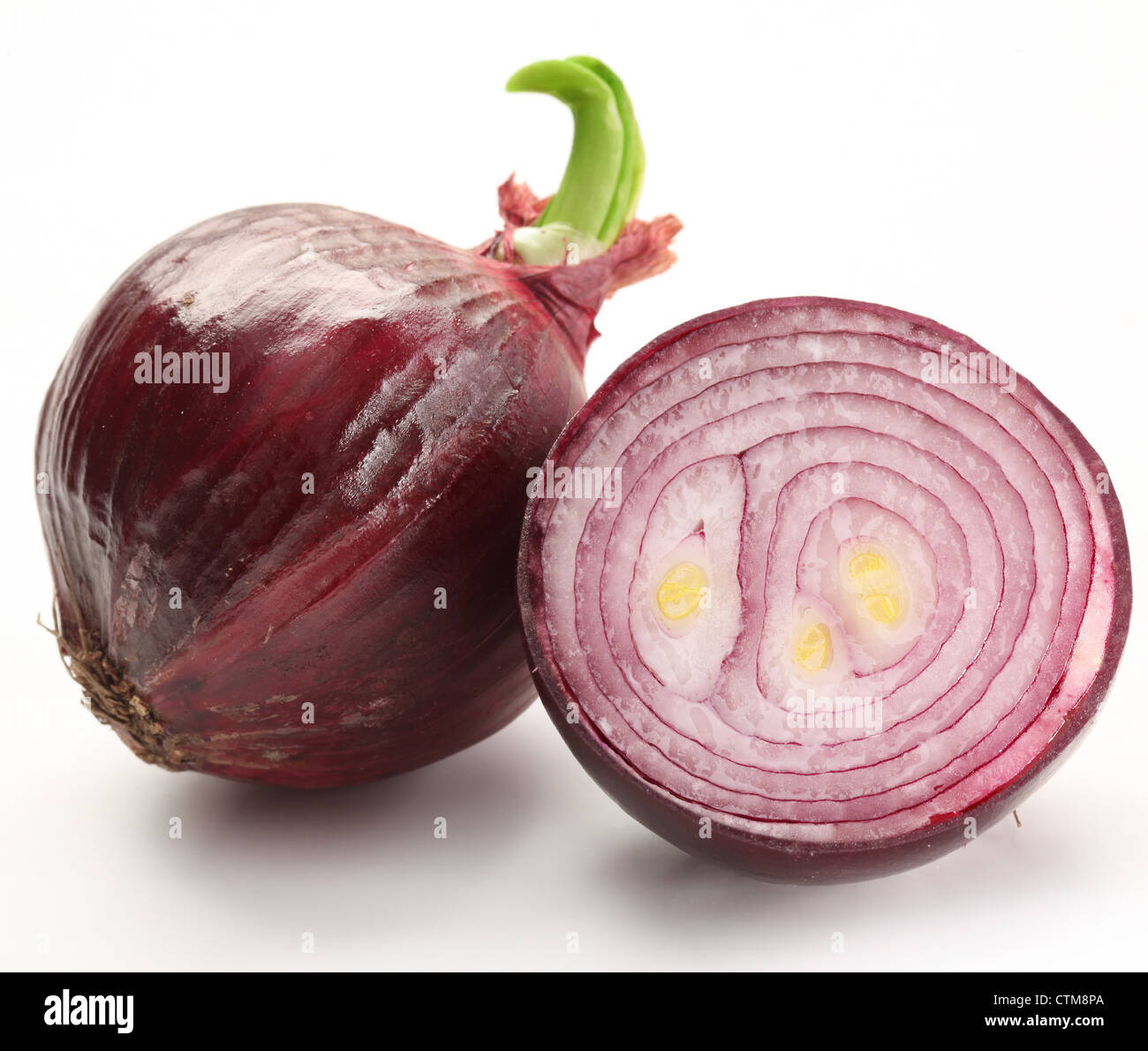 Bulbs of red onion with green leaves on a white background. - Stock Image