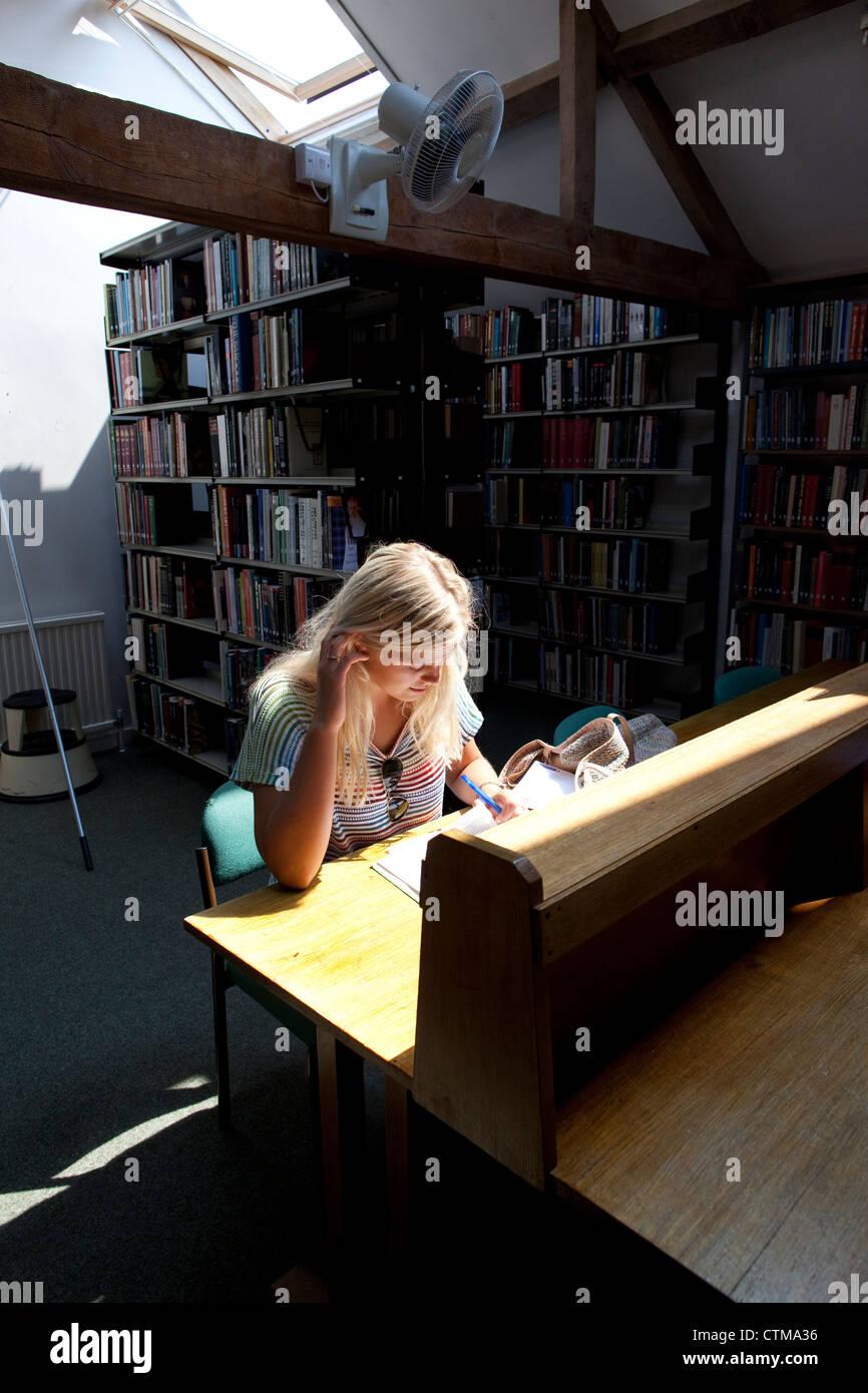 University degree student in library at University of Buckingham, England, UK - Stock Image