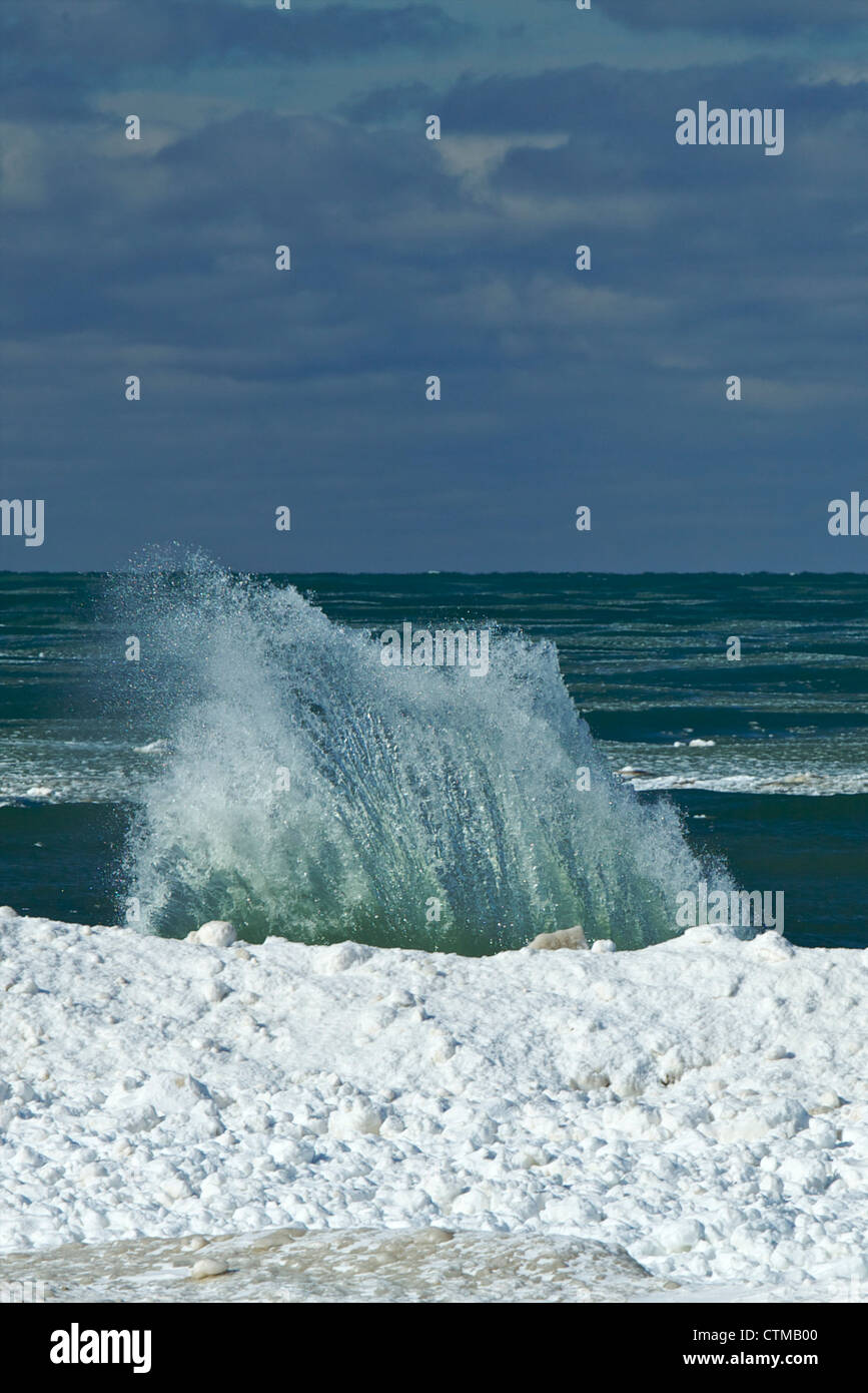 Wave breaking over an icefoot in Lake Michigan Stock Photo