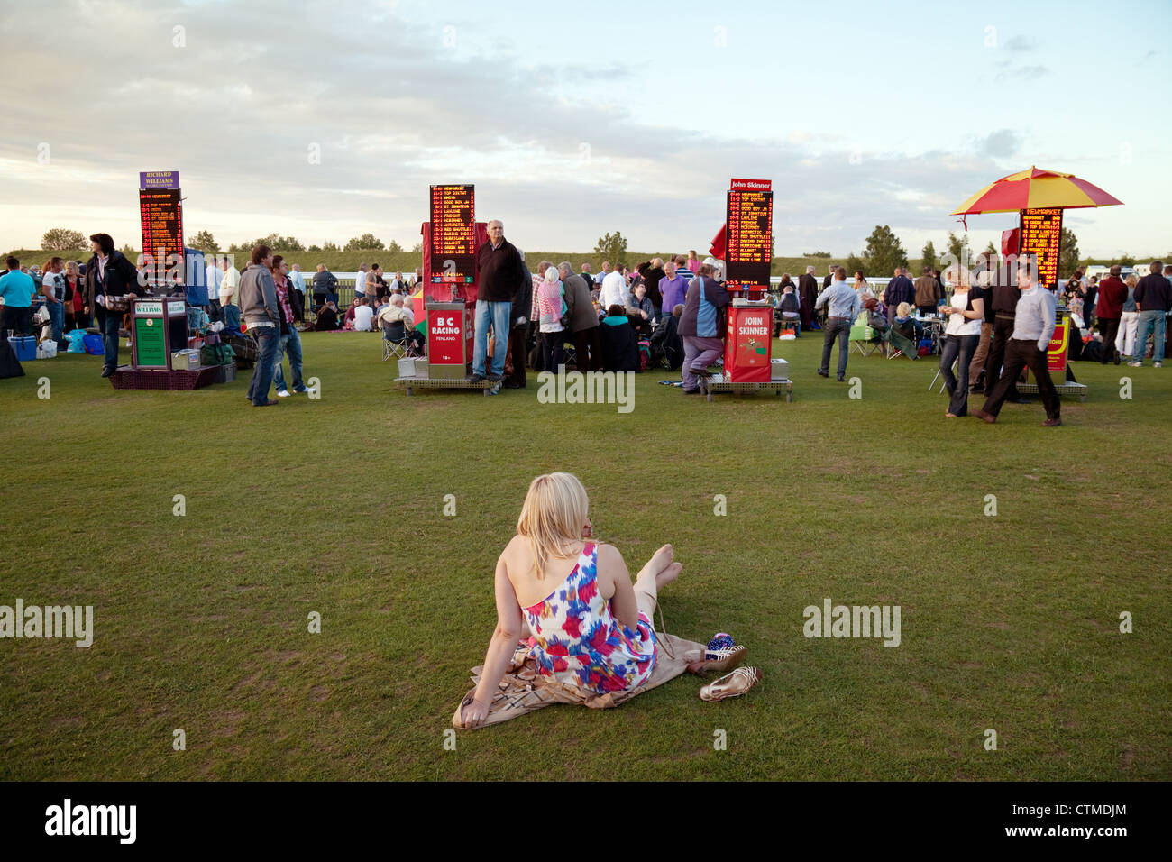 A young woman sitting down at the races, with betting booths, Newmarket July racecourse Suffolk UK - Stock Image