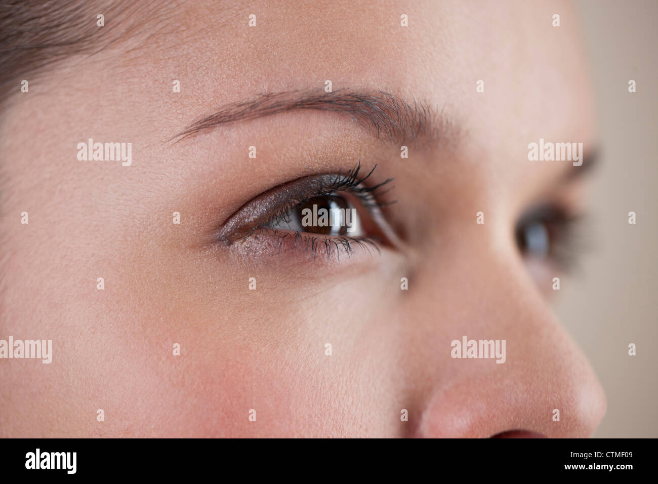 Close-up of a young woman with brown eyes, side view - Stock Image