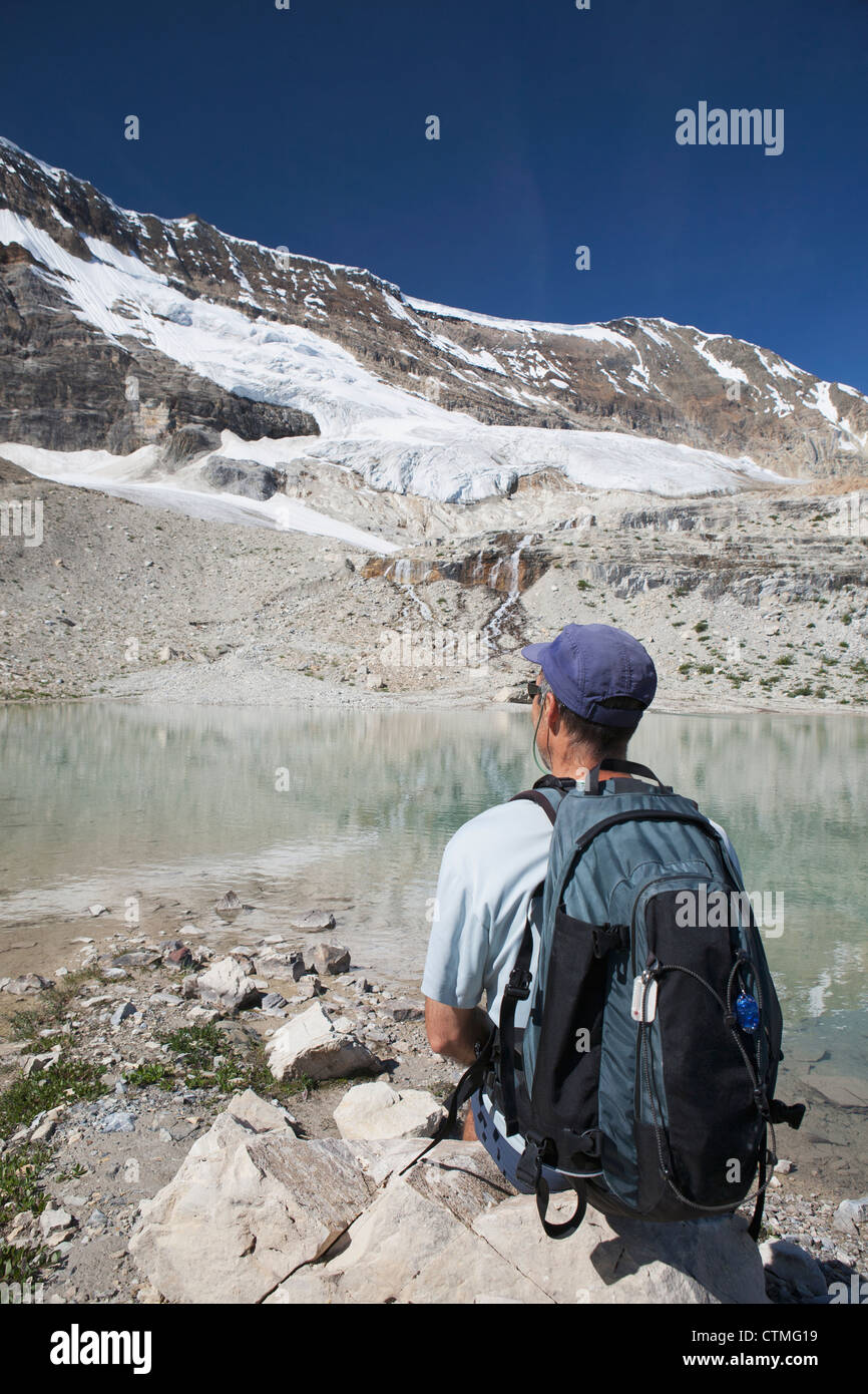 Male Hiker Sitting On A Rock With Glacier On Mountain Side Streaming Down Into A Reflective Mountain Pond, British - Stock Image