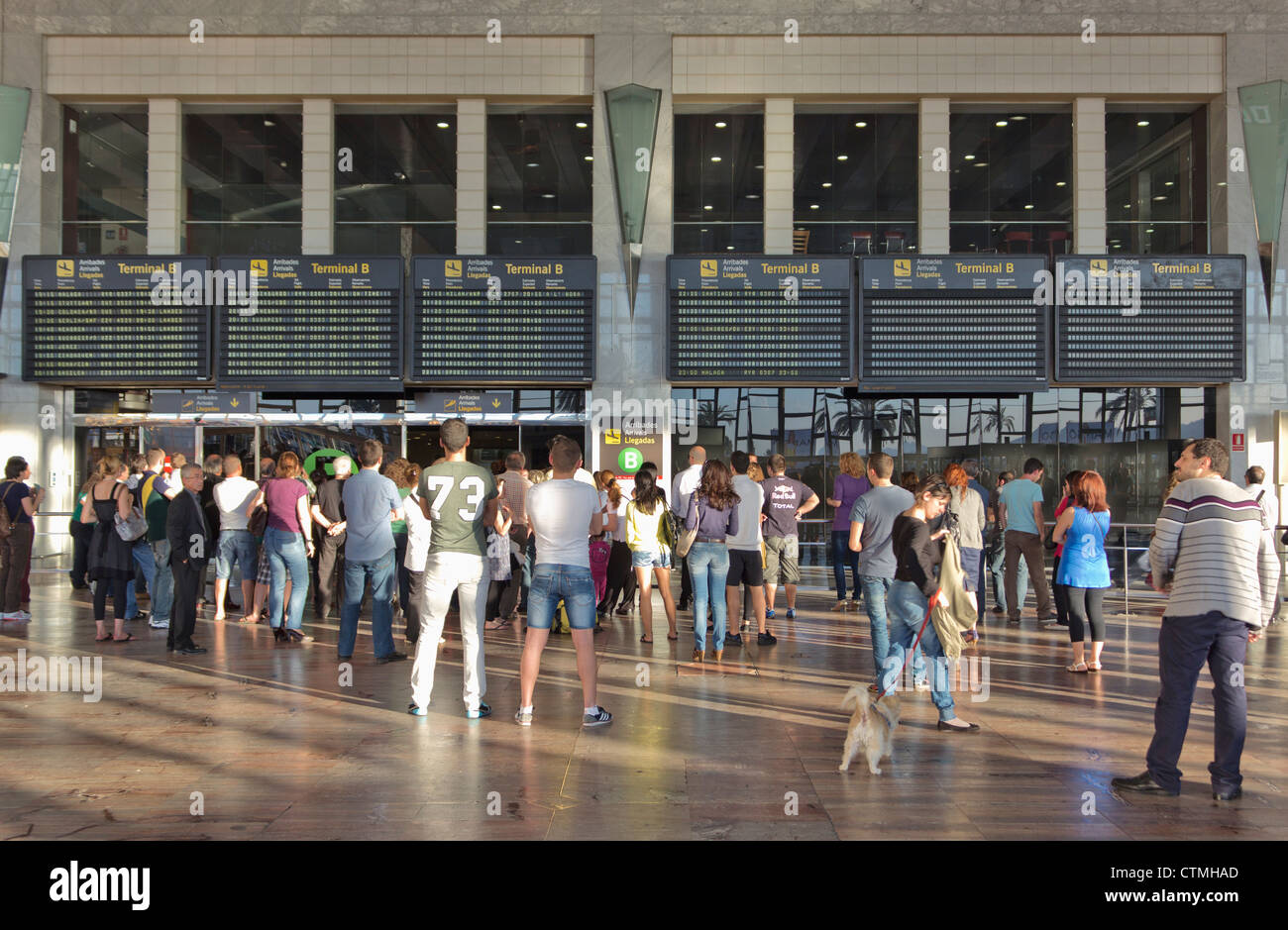 People waiting in the arrivals hall at El Prat Airport, Barcelona, Spain. - Stock Image