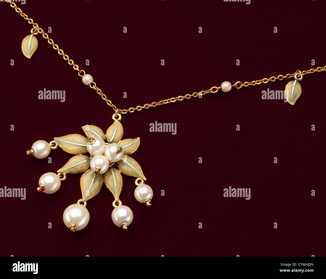 Costume jewelry. A close-up view of a gold necklace with flower and pearls beads. - Stock Image