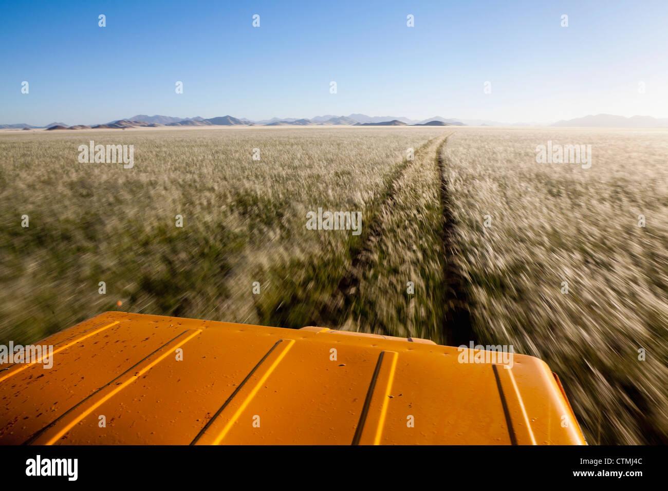 4x4 driving through endless expanse of Namibian grasslands, Namib Rand, Namibia - Stock Image