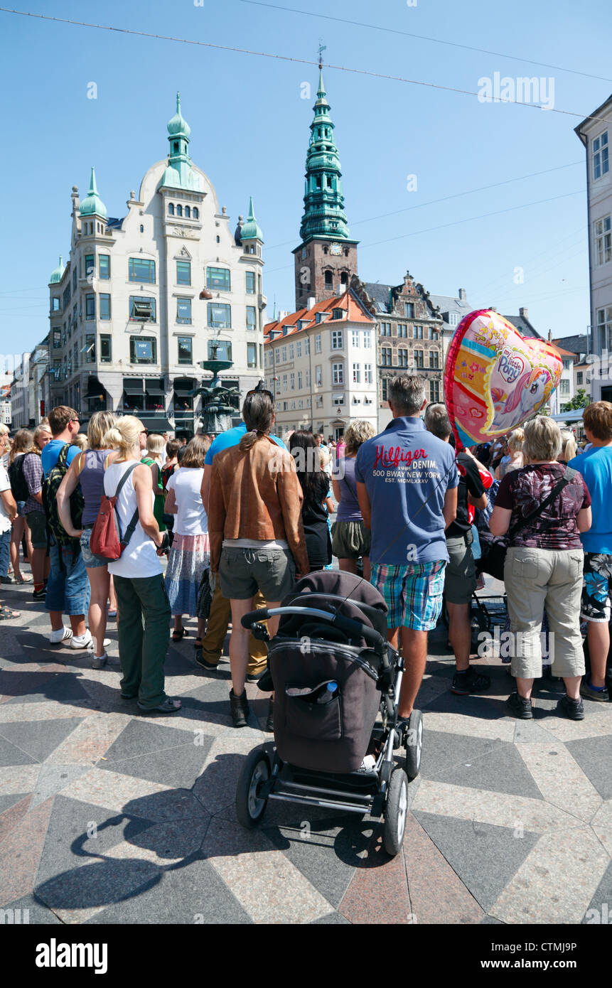 Crowd of people watching street performers at Amagertorv on shopping, entertainment and pedestrian street Strøget - Stock Image