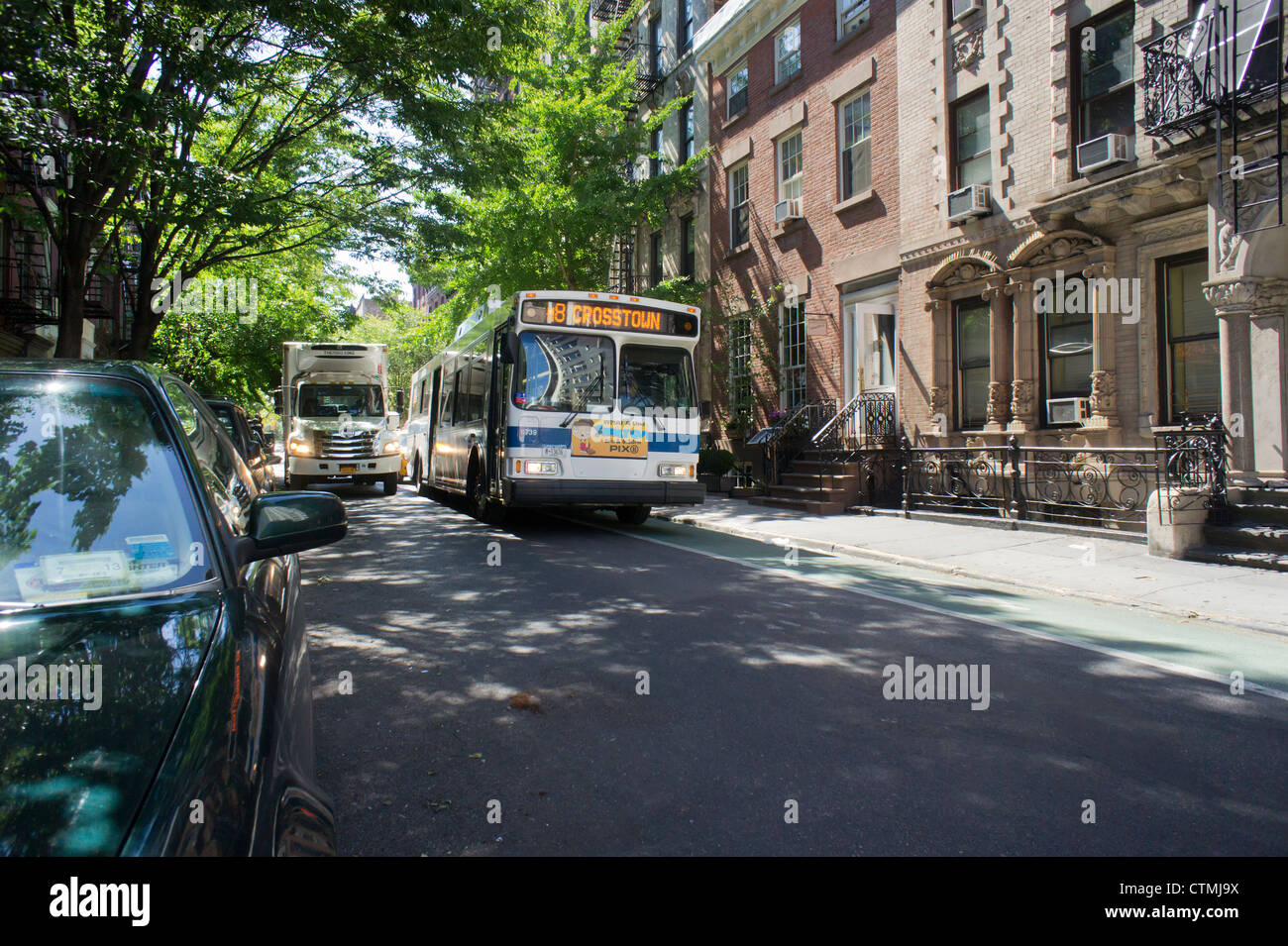 A NYC Transit bus maneuvers through the narrow streets of the Greenwich Village neighborhood of New York - Stock Image
