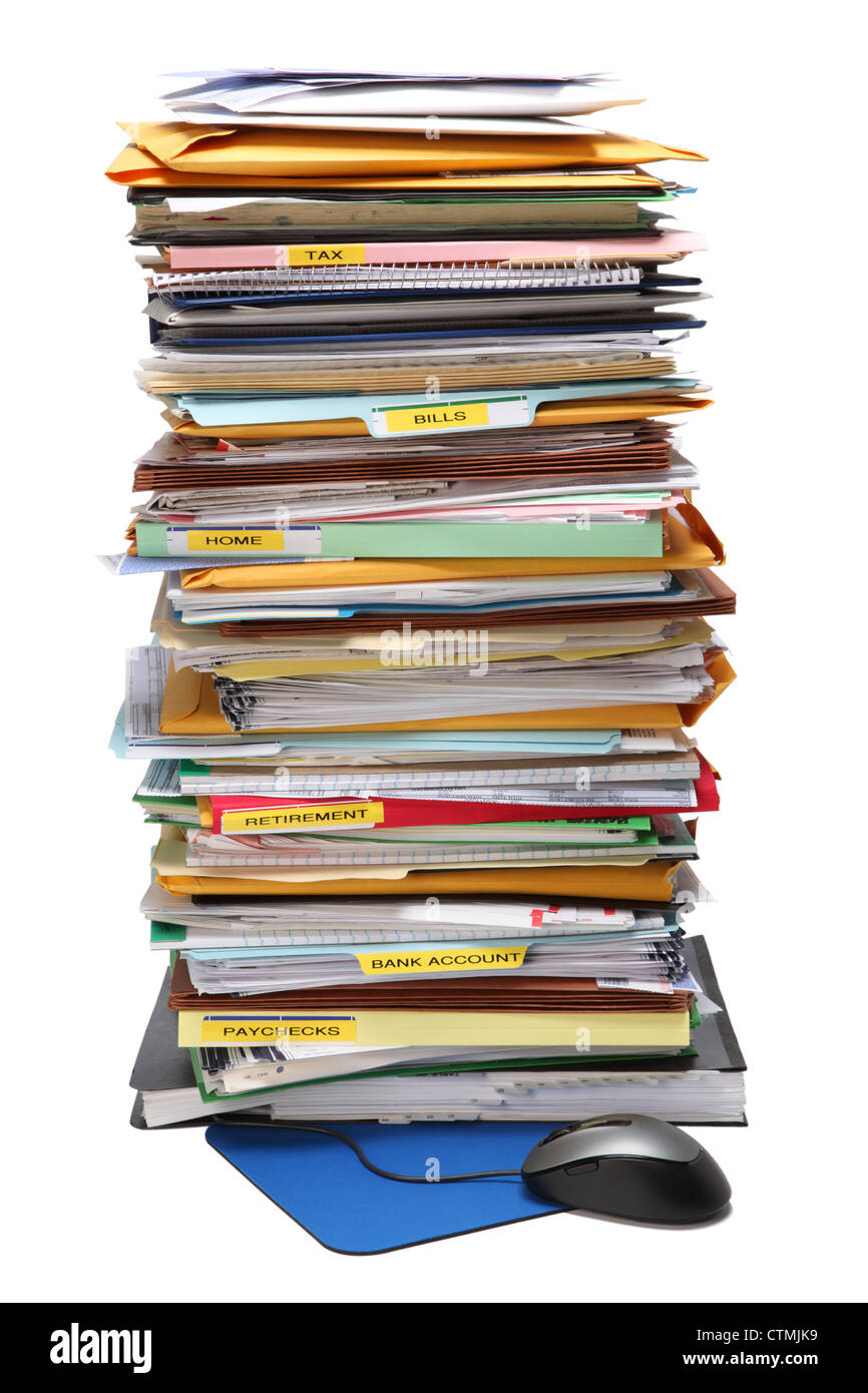 A very tall stack of paperwork in color folders. A Computer mouse and pad at the bottom. - Stock Image