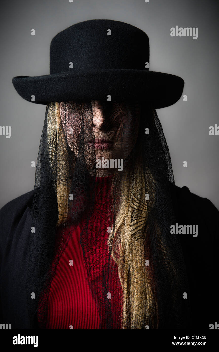 6d739d1272e A young blonde haired girl woman wearing a hat with black victorian  mourning lace covering her face