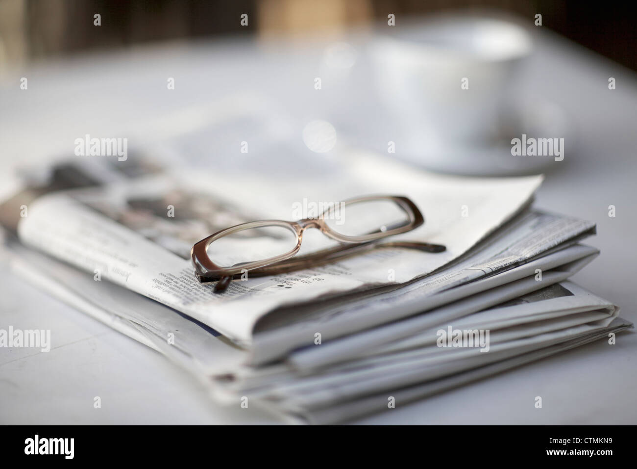 A pair of reading glasses sitting on top of a newspaper, Johannesburg, Gauteng, South Africa Stock Photo