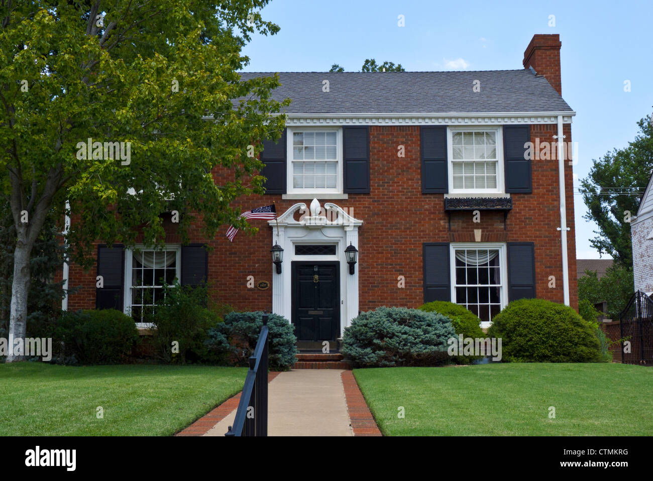 red brick house with flag for independence day in oklahoma. Black Bedroom Furniture Sets. Home Design Ideas