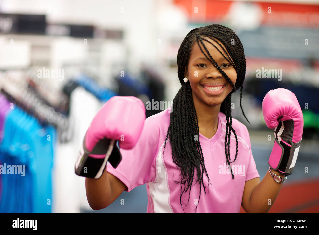 A young woman wearing boxing gloves and looking at the camera, Pietermaritzburg, KwaZulu-Natal, South Africa Stock Photo