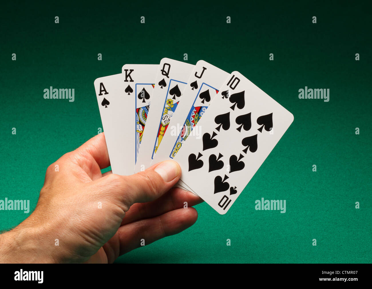 A man's hand holding playing cards on a green table. A Royal Flush of spades in the game of Poker - Stock Image