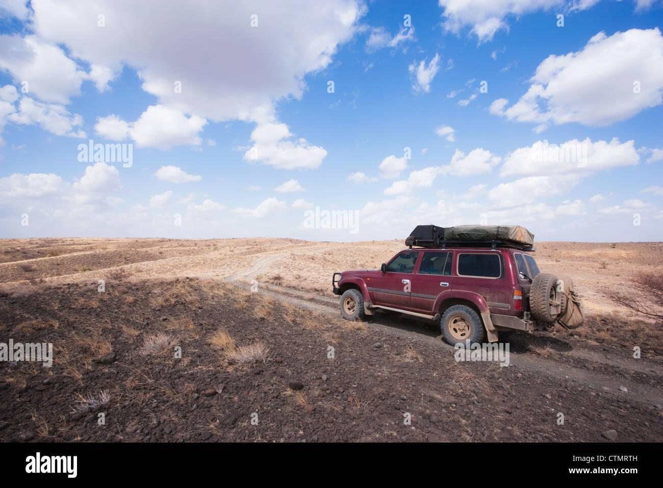Four-Wheel drive on volcanic rocks in desert, Loyongalani region, Lake Turkana, Kenya Stock Photo