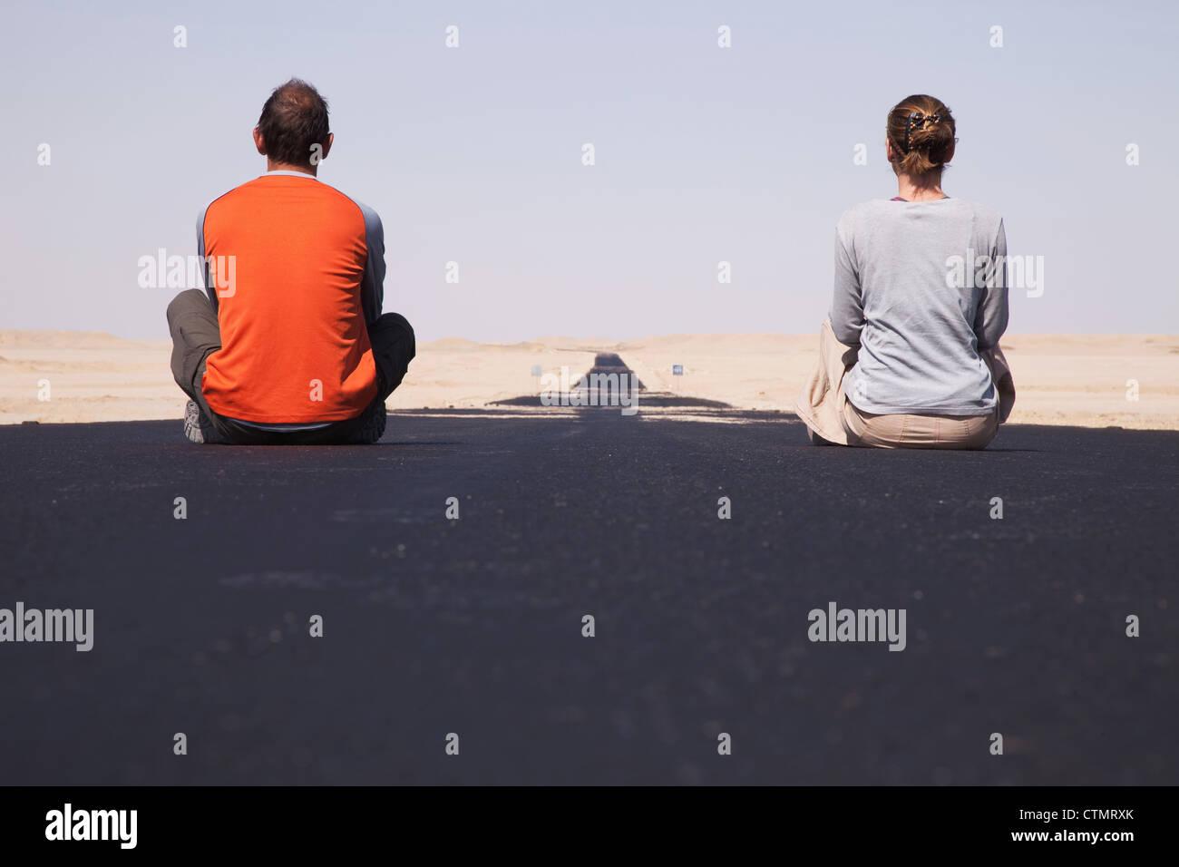 Tourists sitting on Western Desert Road, Abu Minqar, Western Desert, Egypt - Stock Image