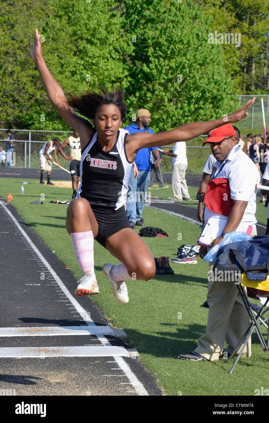 teen doing a high jump during  a high school track and field event in Maryland - Stock Image