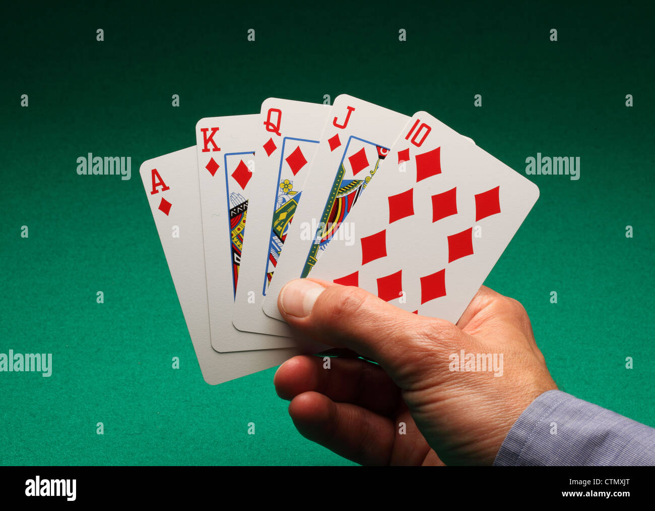 A man's hand holding playing cards on a green table. A Royal Flush of diamonds in the game of Poker - Stock Image