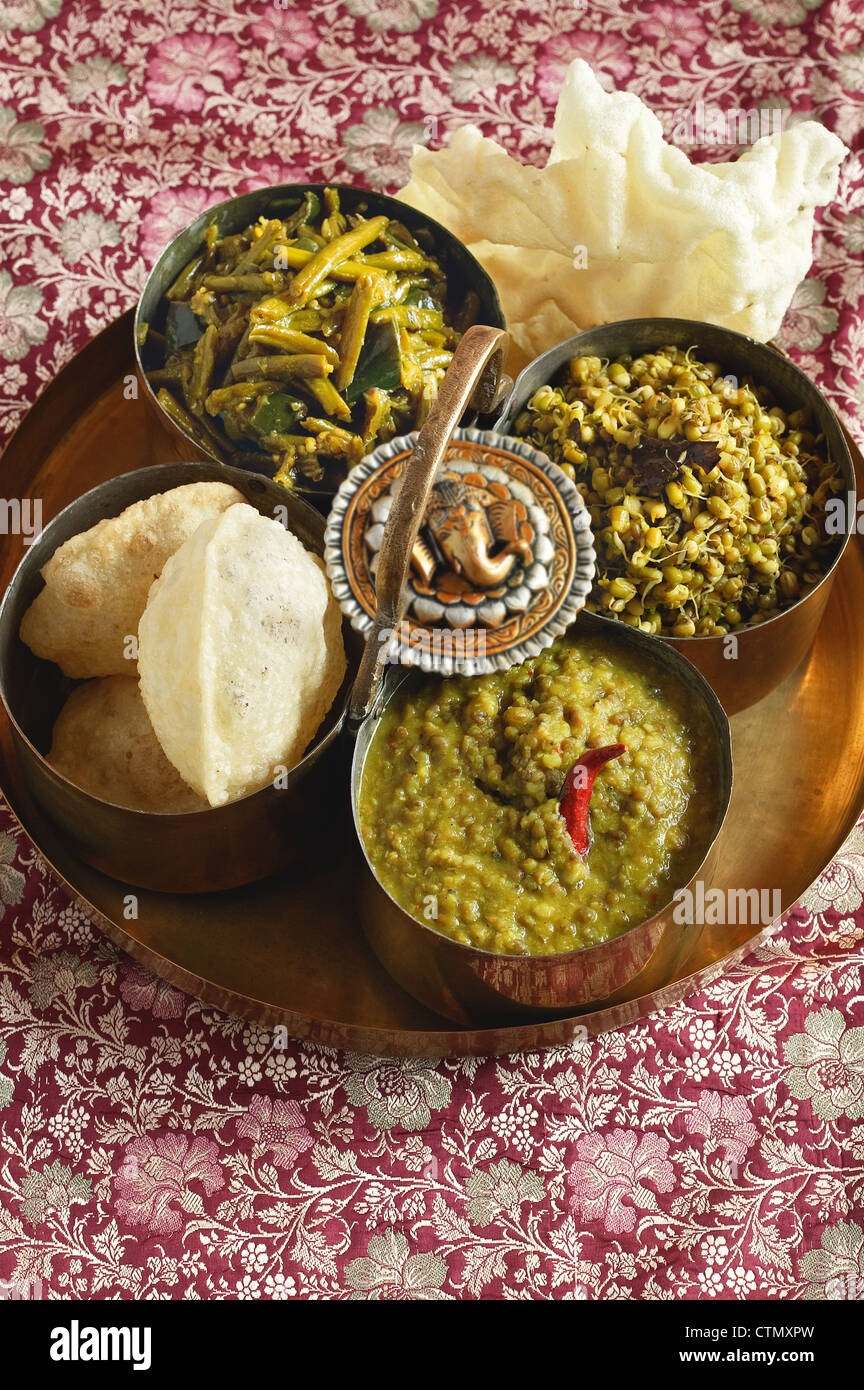 Indian cooking. Moong sprouts, green mung lentils and easy green curry served with puri - Stock Image