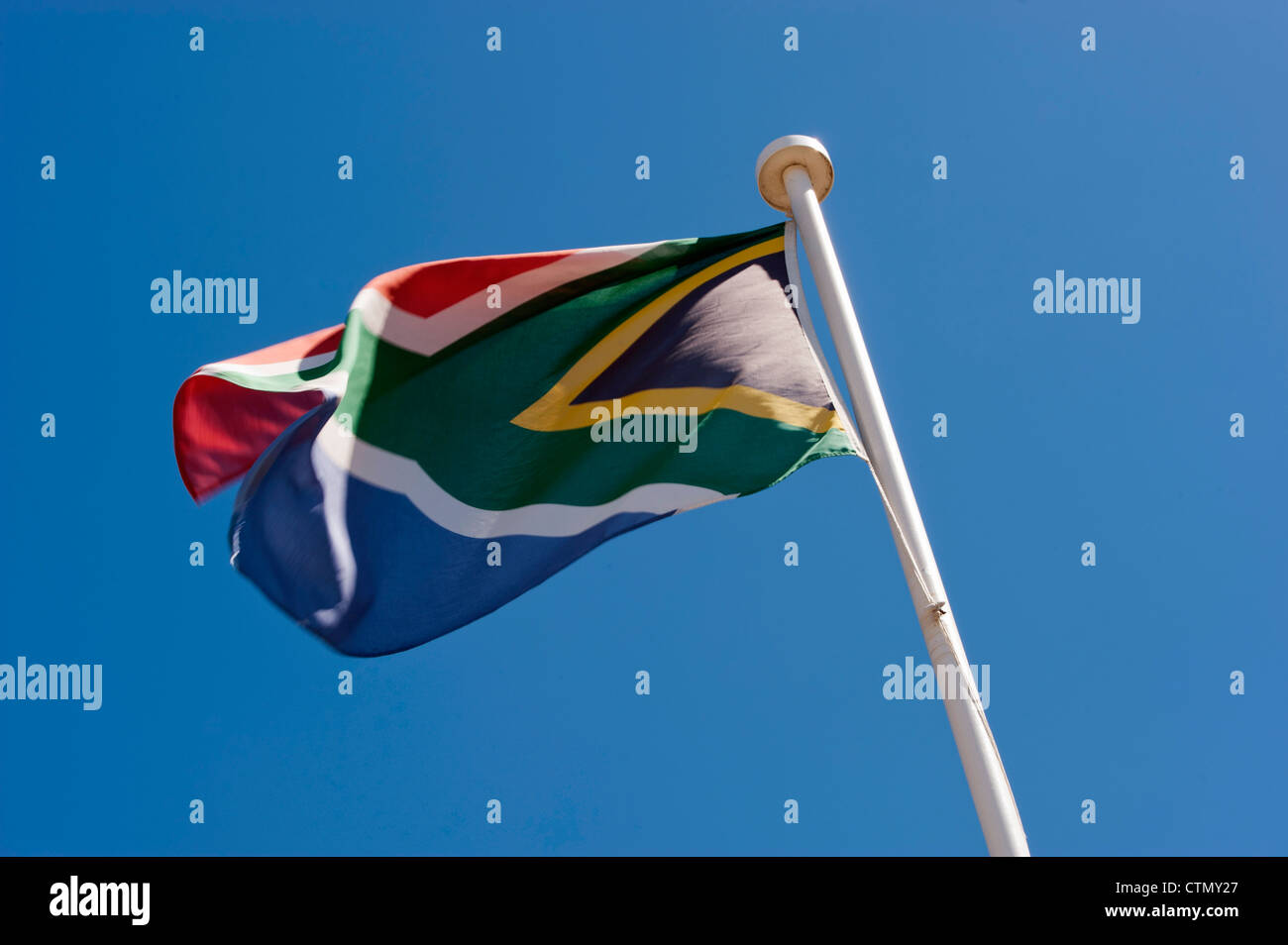 The colourful South African flag fills out in a firm sea breeze, Cape Town, South Africa - Stock Image
