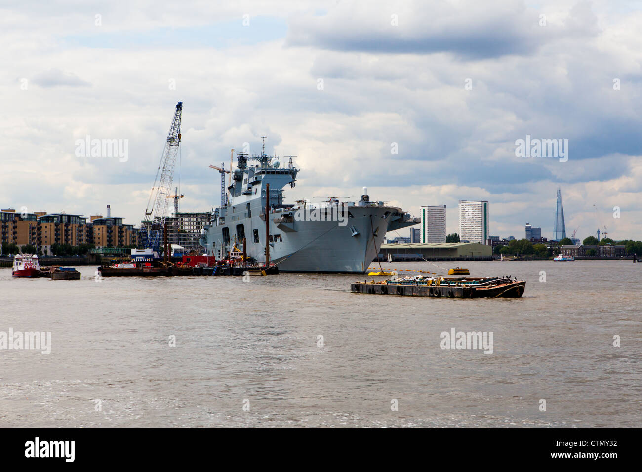 HMS Ocean moored in Greenwich with the City of London behind her Stock Photo