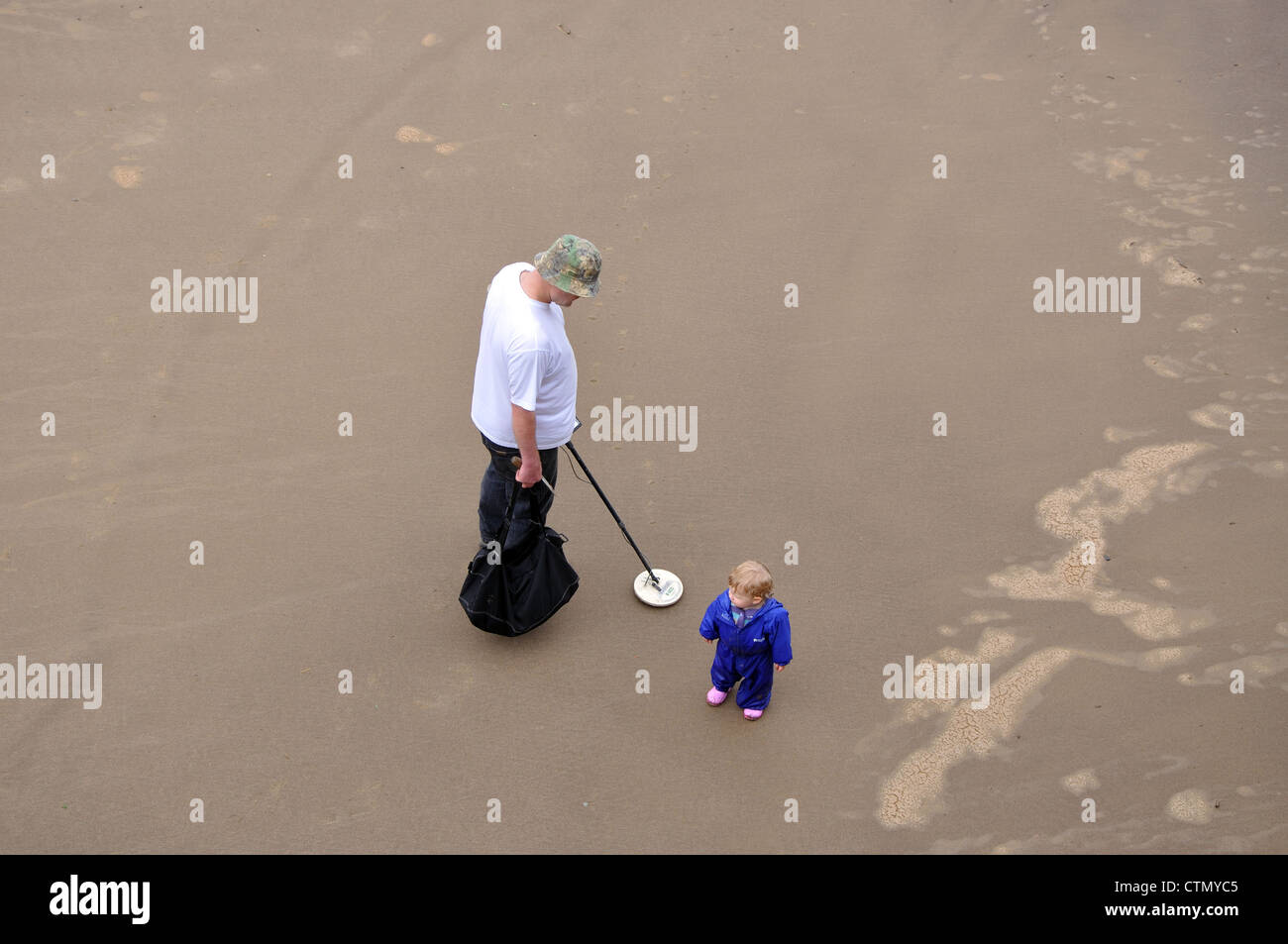 man searching beach with a metal detector, Whitby, North Yorkshire, England, UK - Stock Image