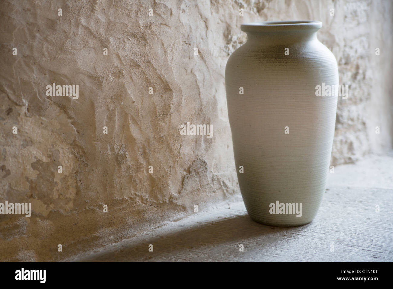 Handmade and smoothed vase in room corner - Stock Image