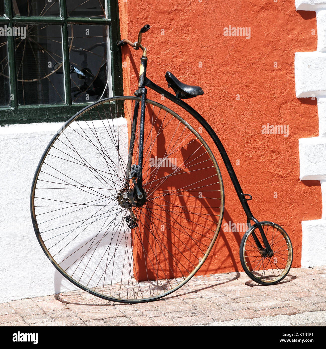 An antique bicycle leaning up against the stucco wall of a building in Bermuda. - Stock Image