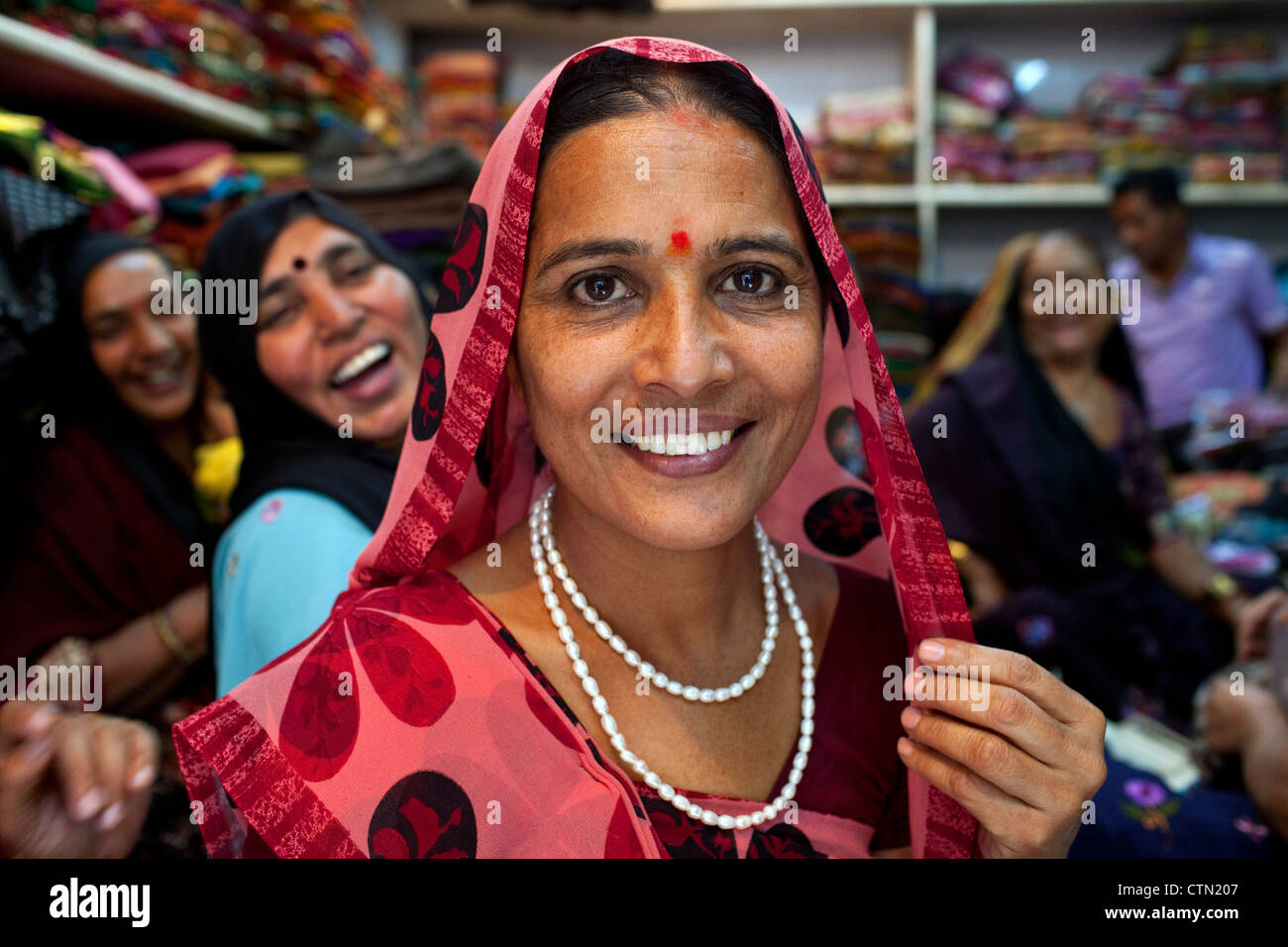 A portrait of smiling pretty Rabari women wearing traditional sari clothes in a textile shop in Ahmedabad, Gujarat - Stock Image