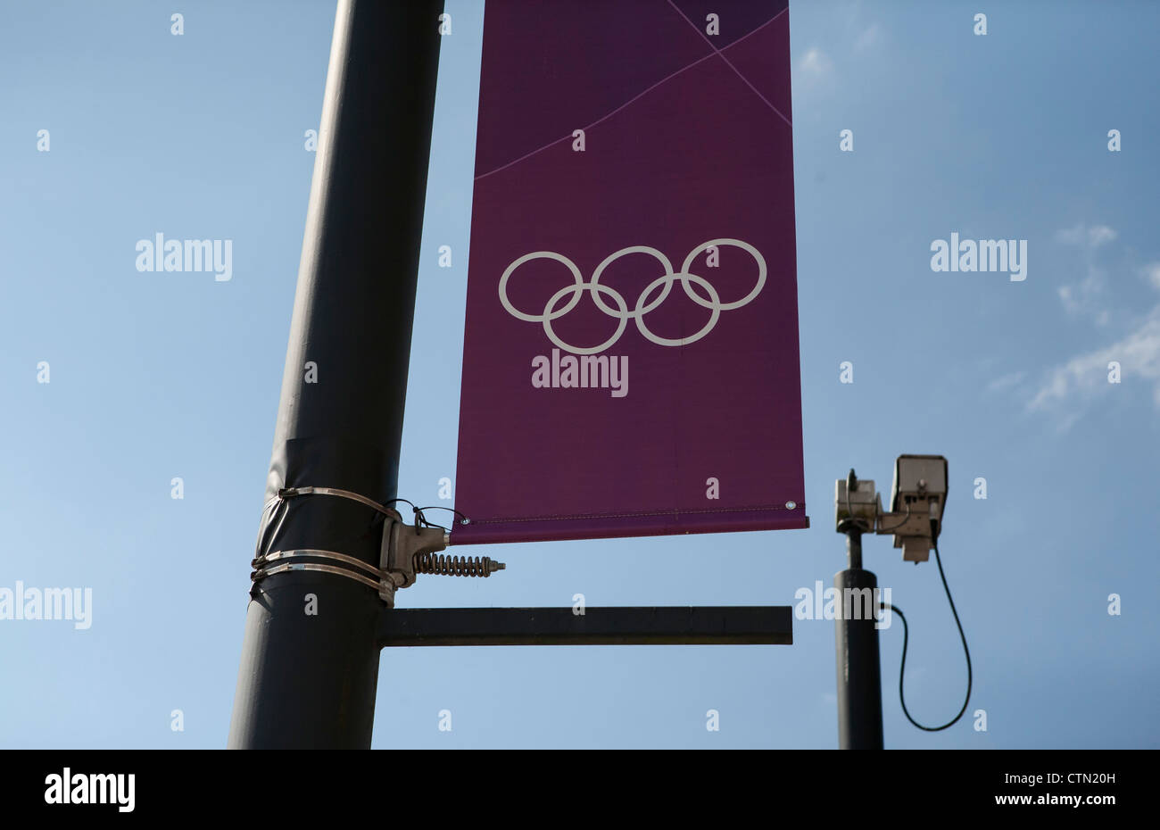 An Olympic flag next to a CCTV camera. Security has been paramount during the 2012 games. - Stock Image