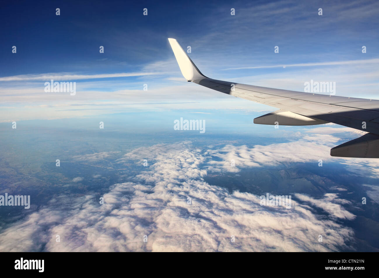 Aerial view on white clouds from airplane (wing view). - Stock Image
