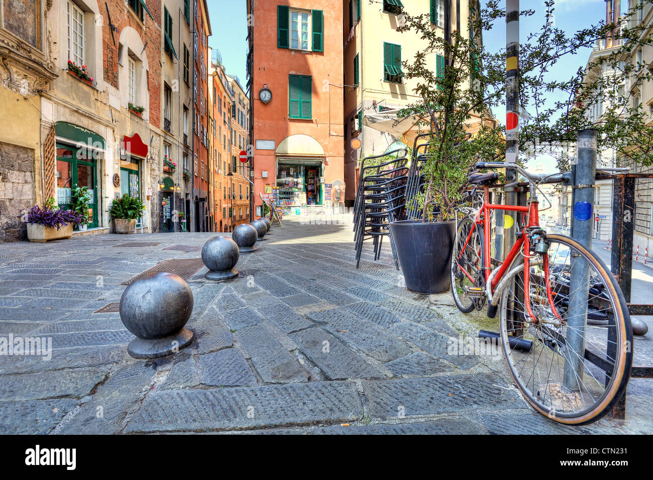 Bicycle and old colorful buildings on background in city of Genoa, Italy. - Stock Image