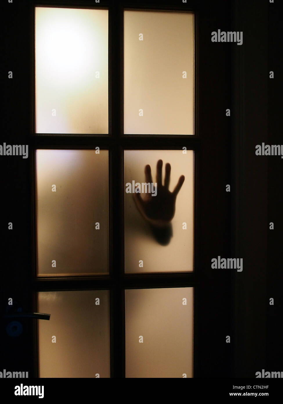 Silhouette of hand on window. Stock Photo