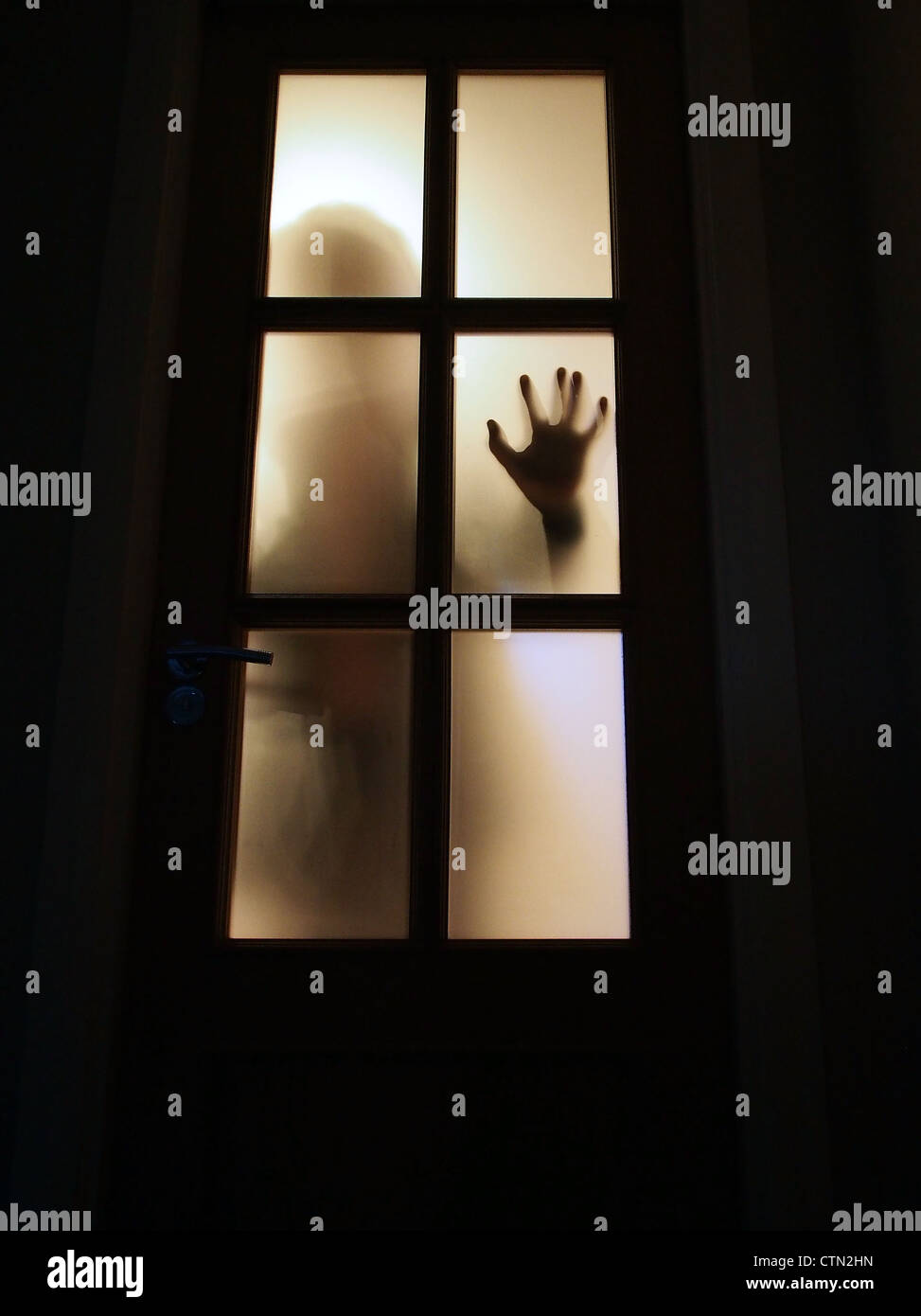 Silhouette of hand on window. - Stock Image