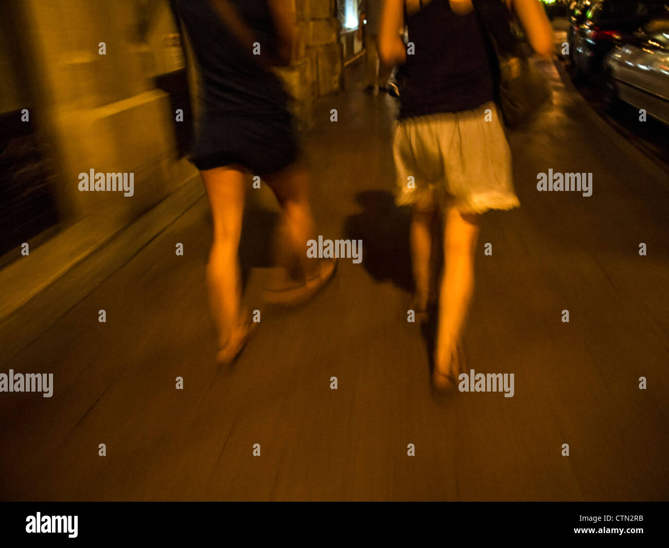 Two women walking by night in an unsafe street - Stock Image