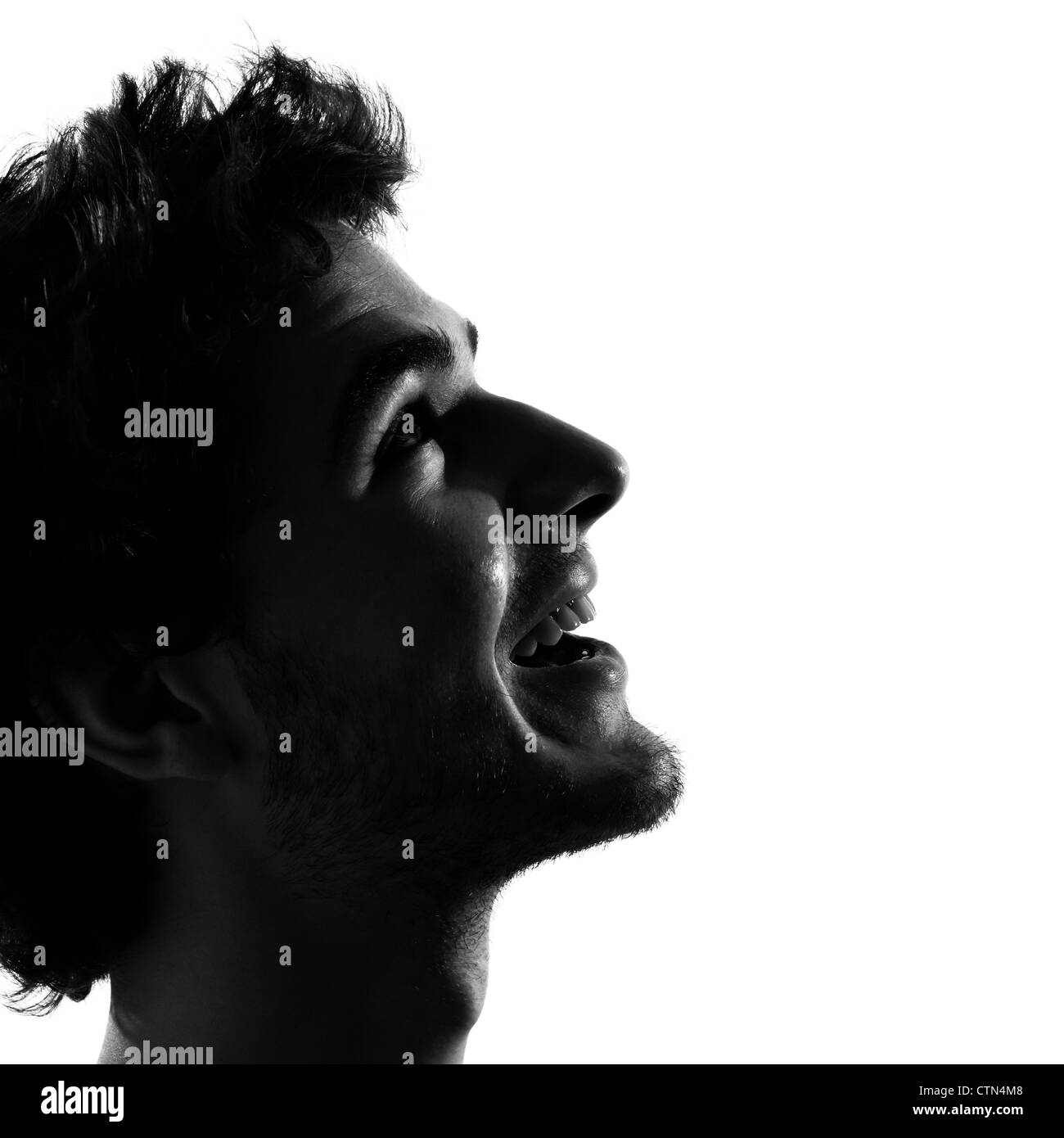 young man looking up smiling happy portrait silhouette in studio isolated on white background - Stock Image