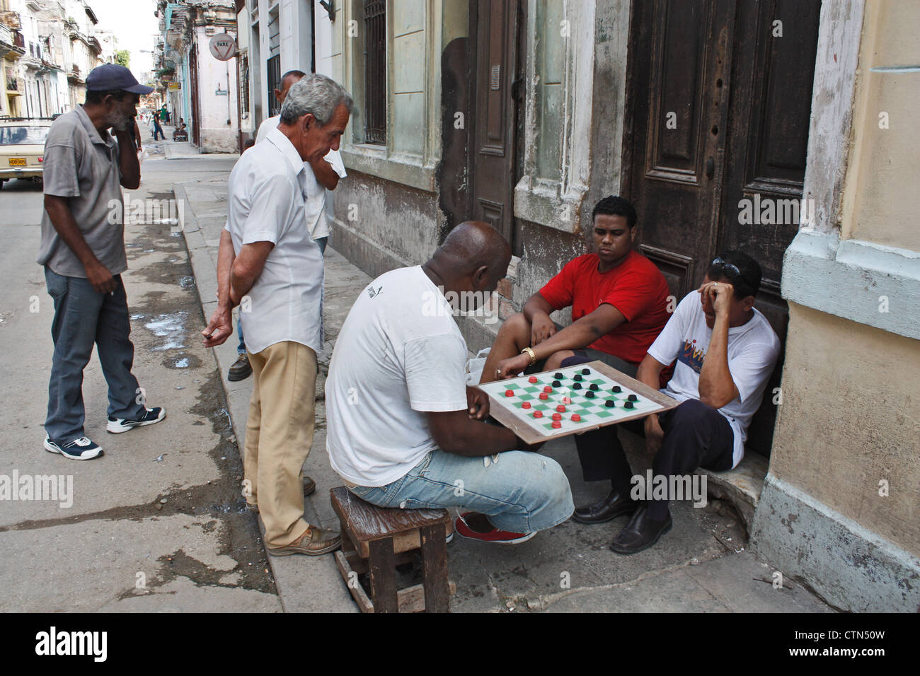 local men play checkers or draughts on the street in downtown havana, cuba - Stock Image