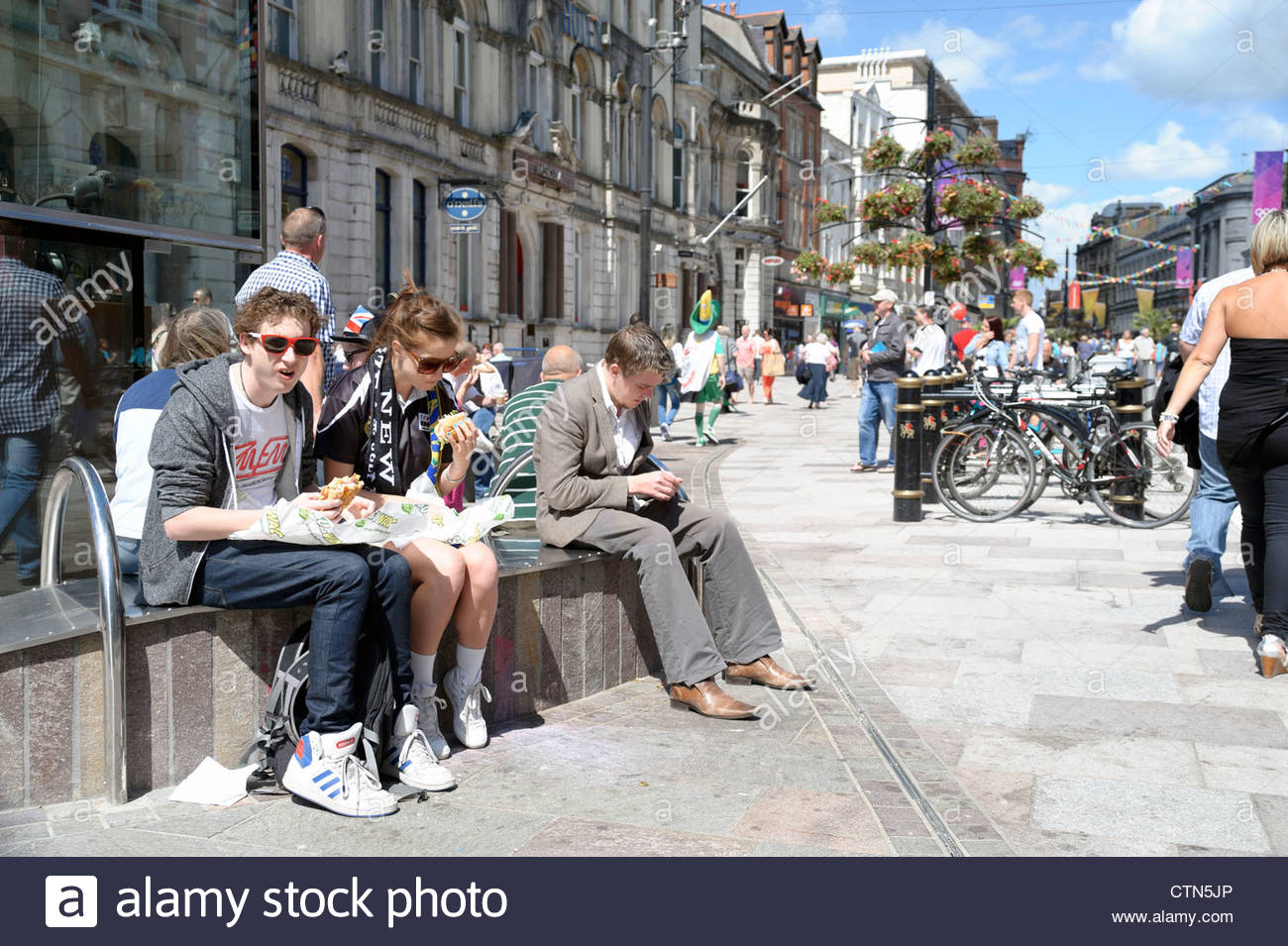 People eating lunch in the streets of Cardiff City Centre, South Wales, UK. - Stock Image