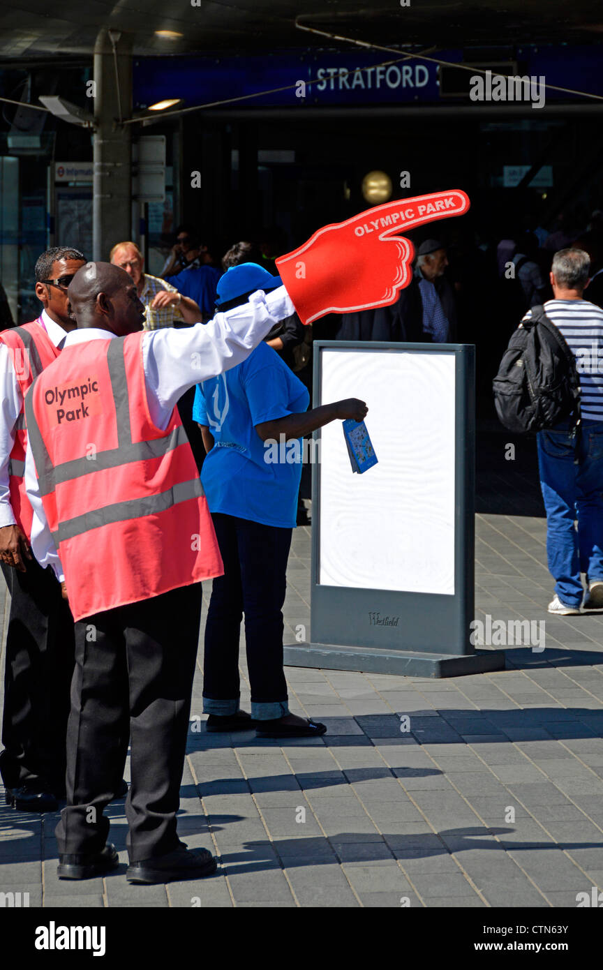 Olympic Park helpers outside Stratford railway station giving pointed directions to the 2012 London Olympic Park - Stock Image