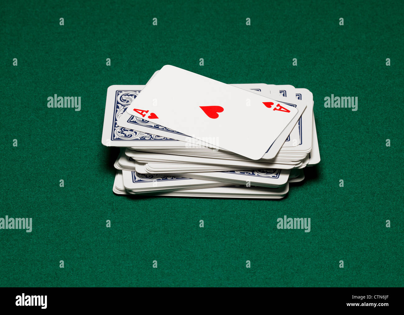A stack of playing cards on a green table. Ace of hearts shown - Stock Image