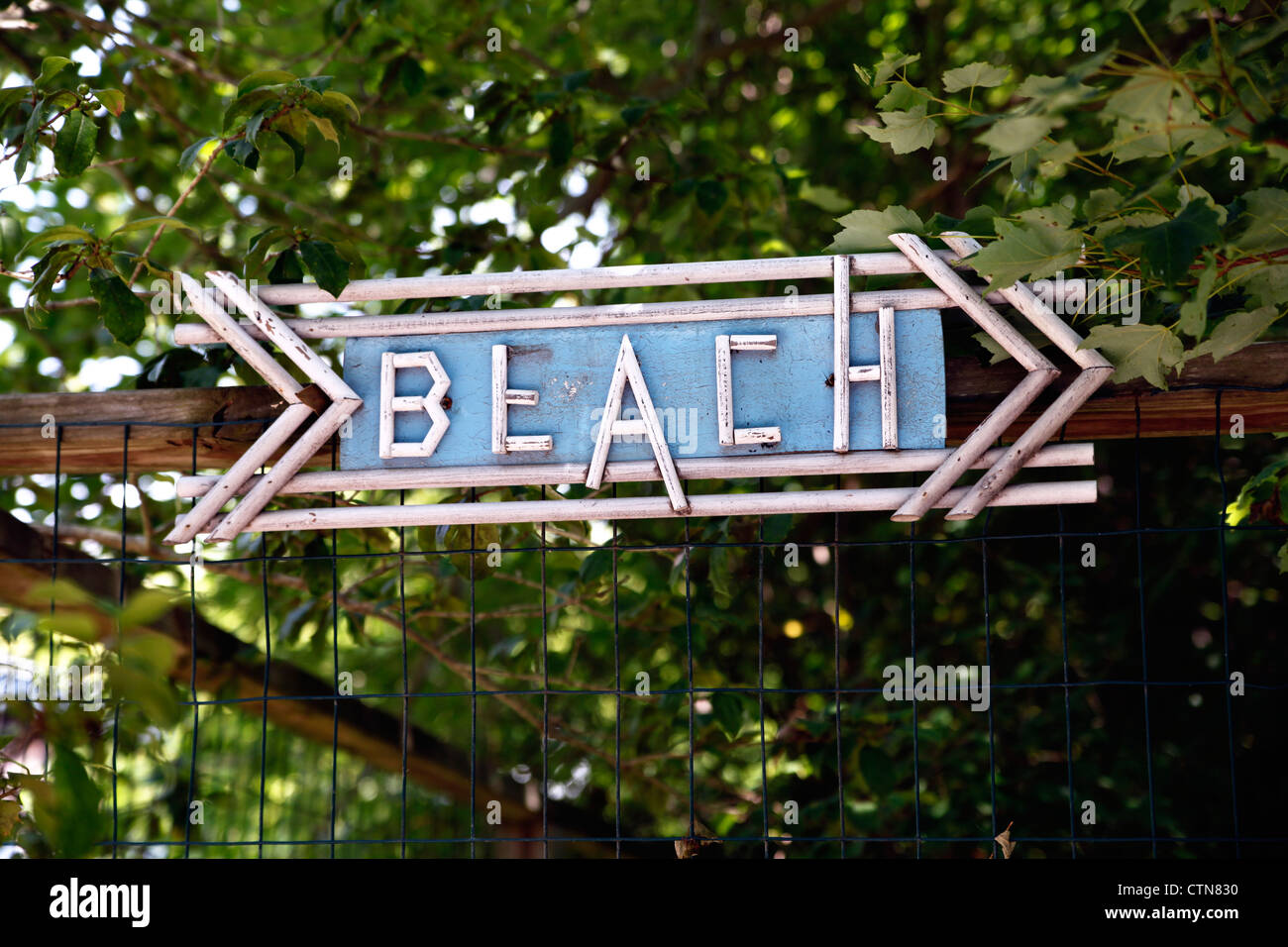 Wooden Sign With Small Wooden Dowel Lettering, Pointing to a Beach - Stock Image
