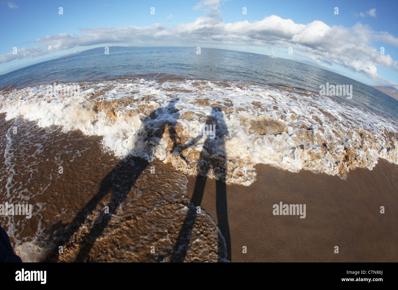 Newlywed couple holding hands with shadows falling across breaking waves on beach. - Stock Image
