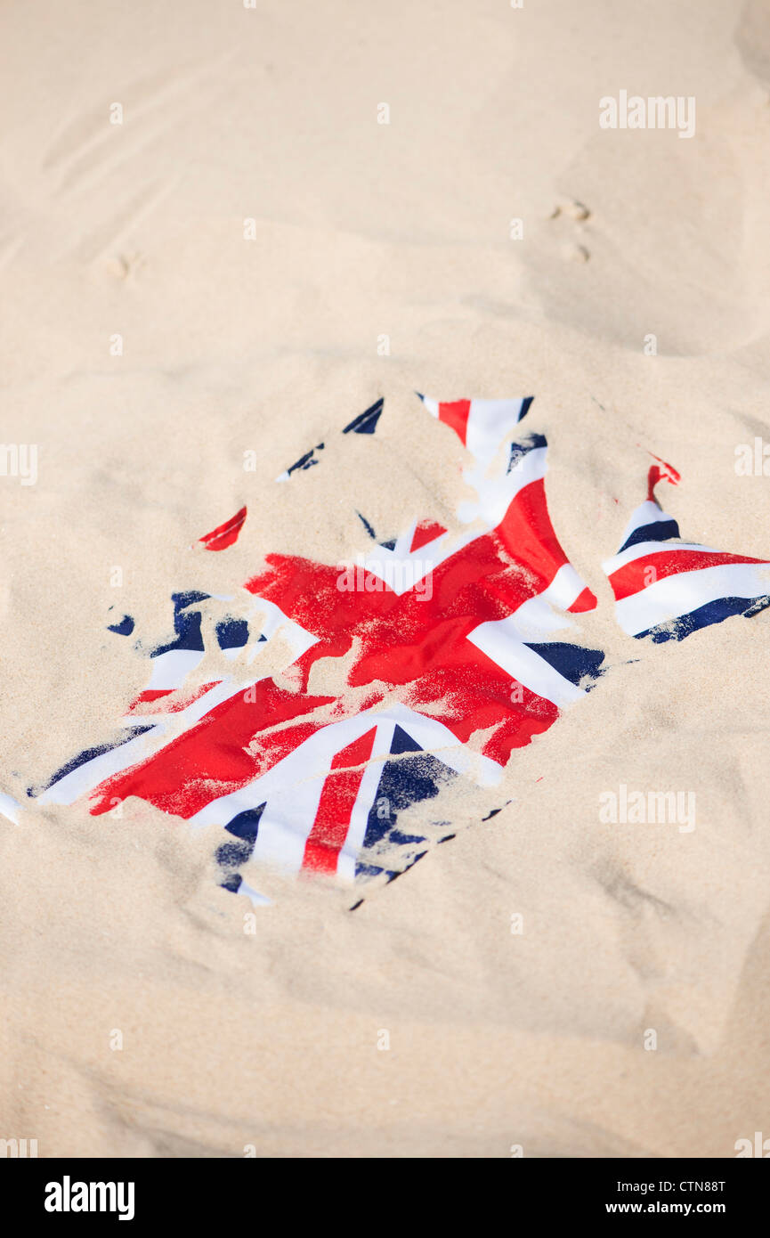 Union Jack flag covered in sand on the beach - Stock Image