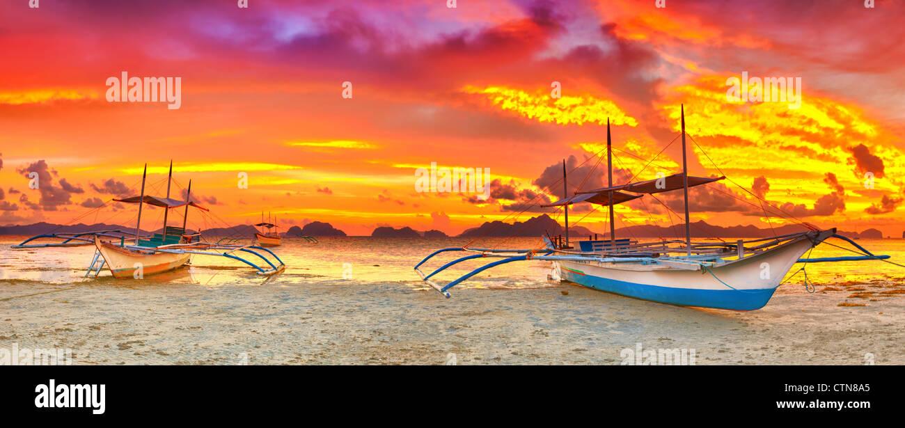 Traditional philippine boat bangka at sunset time - Stock Image