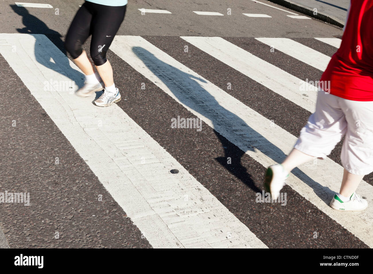 People running or jogging across a road using a zebra crossing, England, UK Stock Photo
