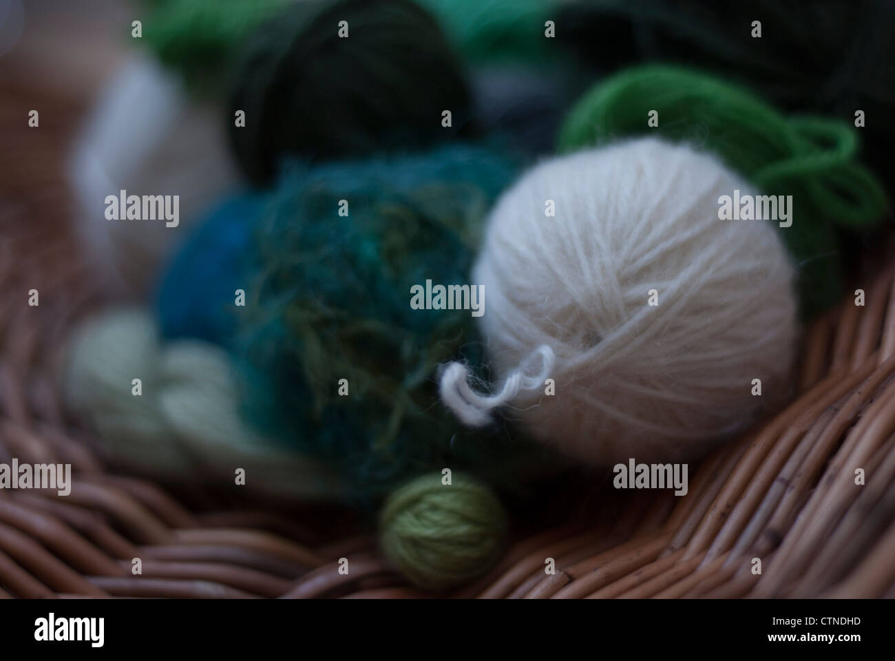 Balls of wool in shades of green, blue and white and on circular willow basket weave Stock Photo