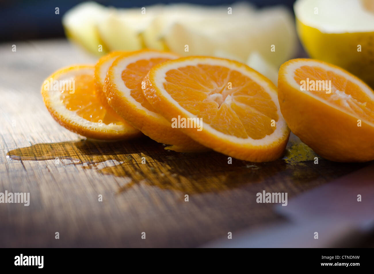 Slices of freshly cut orange on an oak board with out of focus melon in background. - Stock Image
