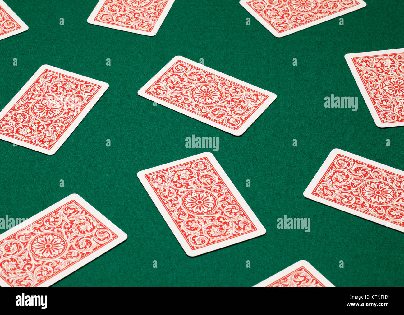 Random playing cards on a green table. - Stock Image