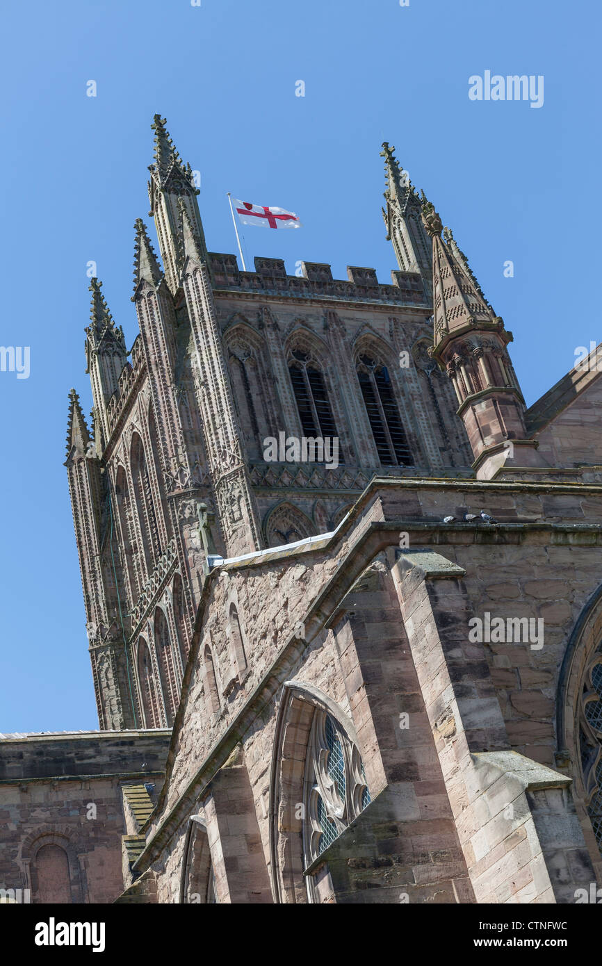 Tower of Hereford Cathedral with battlements and arched windows .The flag of England, the Cross of St. George is - Stock Image